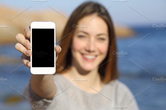 Happy woman showing a smart phone display on the beach.jpg - Technology