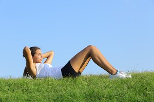 Pretty woman doing crunches on the green grass.jpg