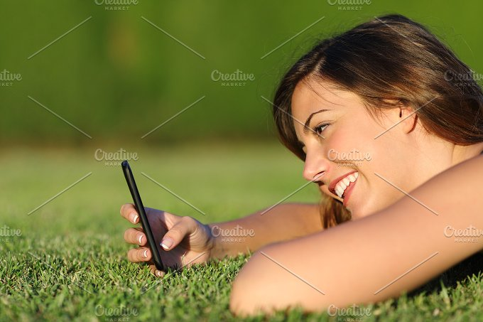 Profile of a funny girl using a smart phone on the grass.jpg - Technology