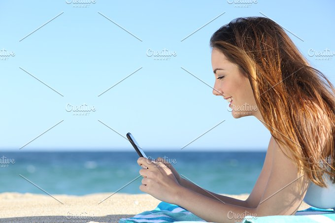 Profile of a woman texting in a smart phone on the beach.jpg - Technology