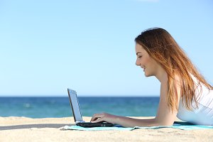 Side view of a teenager girl browsing a laptop on the beach.jpg