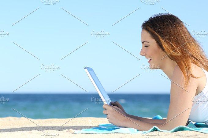 Teenager girl browsing social media on a tablet on the beach.jpg - Technology