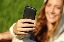 Teenager girl hand using a smart phone with her face in the background.jpg