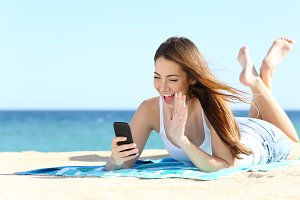 Teenager girl waving during a smart phone video call in vacations.jpg