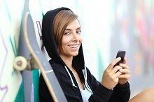 Teenager skater girl using a smart phone looking at camera.jpg