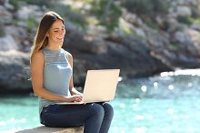 Woman typing on a laptop in a tropical beach.jpg