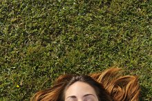 Top view of a woman lying on the grass texting on a smart phone.jpg