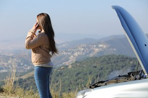 Woman on the phone asking for assistance beside her crashed breakdown car.jpg