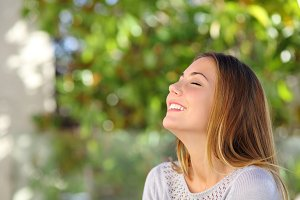 Young happy smiling woman doing deep breath exercises.jpg
