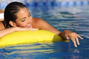 Woman bathing and playing with water on a swimming pool in vacations.jpg