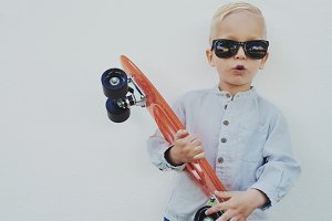 Little hipster boy with a skateboard