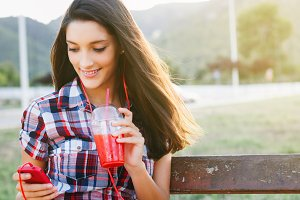Girl drinking red smoothie in park