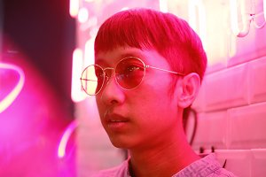 Young asian man in pink neon