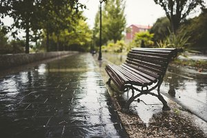 Bench in a promenade in a rainy day