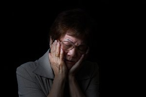 Senior woman holding face in pain
