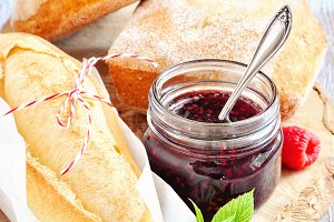 Fresh bread and jam in jars