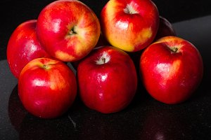Red apples on black surface