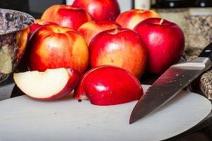 Red apples being sliced on board