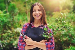Female gardener pruning the plants