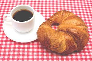Coffee and croissant on table