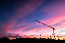 Construction crane over sunset sky by  in Industrial