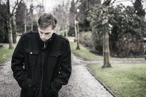 sad troubled man walking outdoors