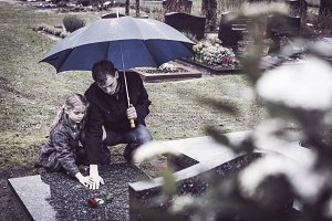 Father and daughter visiting grave
