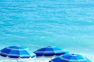 blue shore with blue parasols