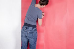 Woman wallpapering the wall