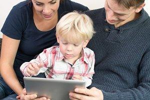 happy family using iPad with boy