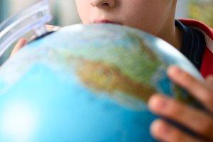 boy looking at globe