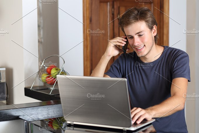 Man on the phone working with a laptop at home.jpg - Technology