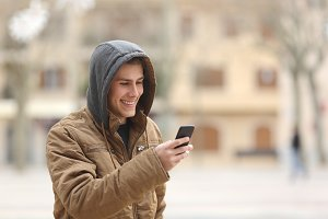 Happy teen walking and using a smart phone.jpg