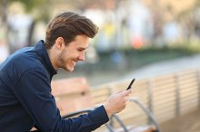 Happy guy using a smart phone in a park.jpg