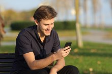 Man using a smartphone sitting on a bench in a park.jpg