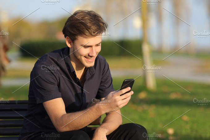 Man using a smartphone sitting on a bench in a park.jpg - Technology