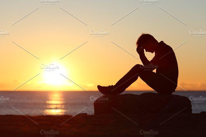 Sad man silhouette worried on the beach.jpg - People