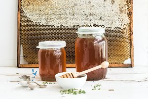 Jars of honey on white rustic table