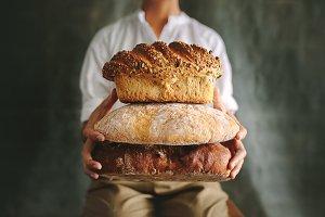 Baker showing various loaf breads