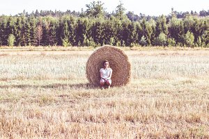 Girl leaning against hay bale