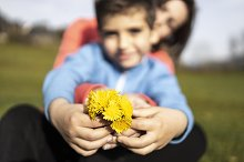 Son giving a bunches of wild flowers by  in People
