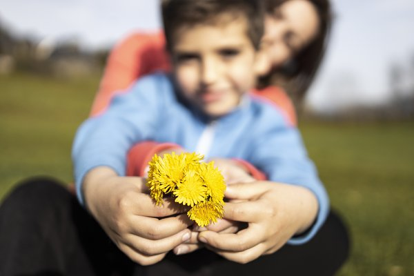 People Images: Cosca - Son giving a bunches of wild flowers