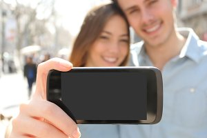 Couple makin a selfie photo with a smartphone and showing screen.jpg