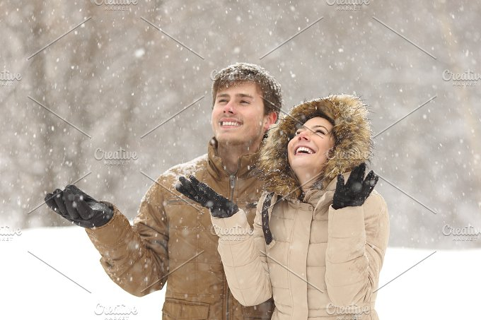 Funny couple watching snow in winter.jpg - Holidays