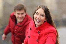 Happy couple running towards camera in winter.jpg
