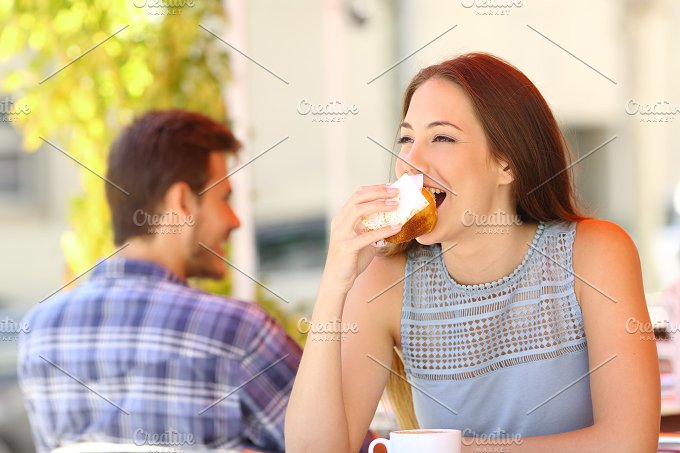 Woman eating a cupcake in a coffee shop.jpg - Food & Drink