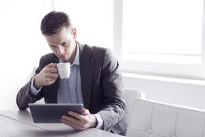 Businessman with coffee and iPad