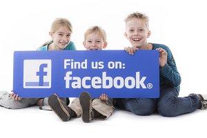 kids holding Facebook sign