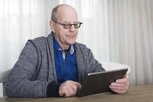 elderly man using a tablet pc