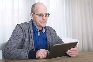 older man using tablet pc